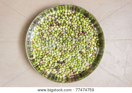 raw pigeon peas kept in a stainless steel plate for drying on a plain background