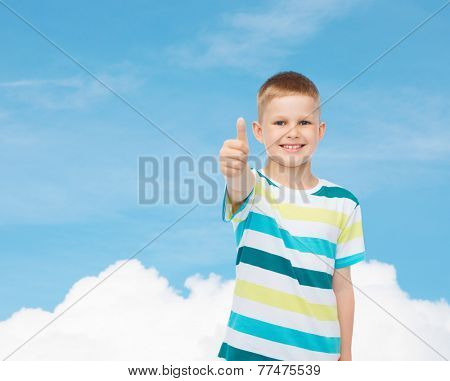 happiness, childhood and people concept - smiling little boy in casual clothes showing thumbs up over blue sky background