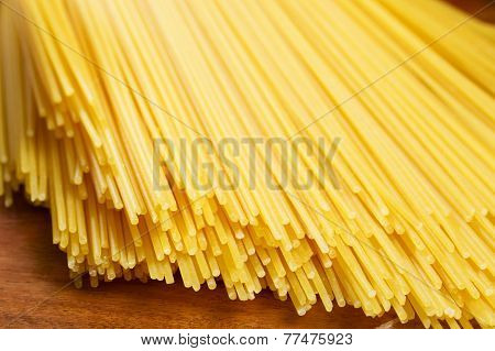 Bunch of spaghetti on wooden brown background
