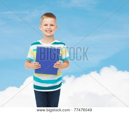 education, childhood and school concept - smiling little student boy with blue book over blue sky background