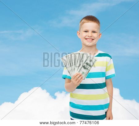 financial, planning, childhood and educational concept - smiling boy holding dollar cash money in his hand over blue sky background