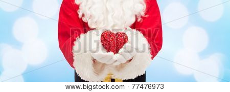 christmas, holidays, love, charity and people concept - close up of santa claus with heart shape decoration over blue lights background