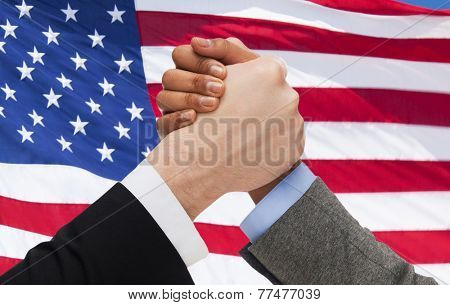 partnership, politics, gesture and people concept - close up of two hands arm wrestling over american flag