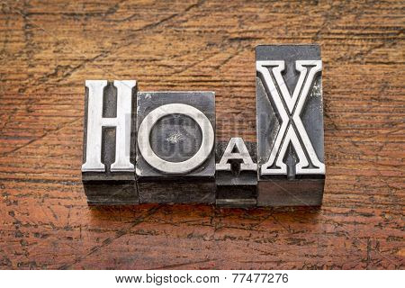 hoax word in mixed vintage metal type printing blocks over grunge wood