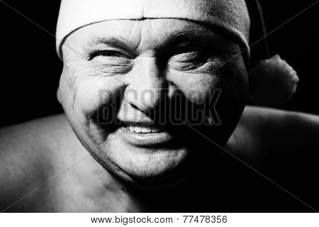 Close up black and white portrait of laughing mature man in Santa Claus hat