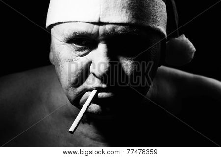 Close up black and white portrait of ominous mature man in Santa Claus hat and with cigarette in his mouth