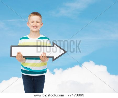 advertising, direction and childhood concept - smiling little boy with white blank arrow pointing right over blue sky