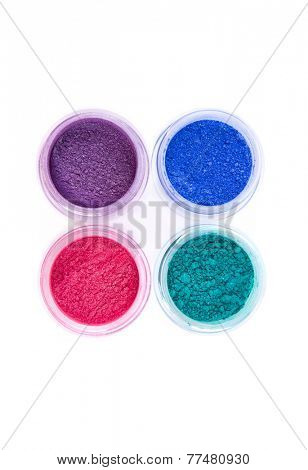 Jars with loose eye shadows in pastel colors, top view isolated on white background