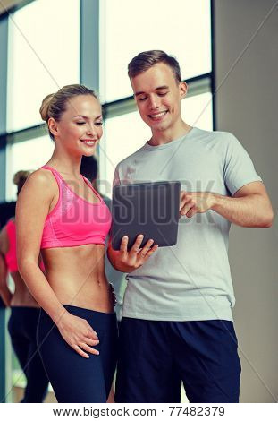 fitness, sport, exercising, technology and diet concept - smiling young woman and personal trainer with tablet pc computer in gym