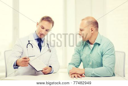 healthcare and medicine concept - serious doctor with clipboard and patient in hospital