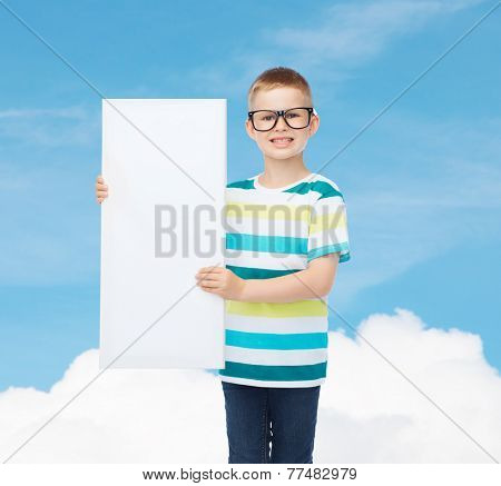 vision, health, advertisement and childhood concept - smiling little boy in eyeglasses with blank board over blue cloudy sky background