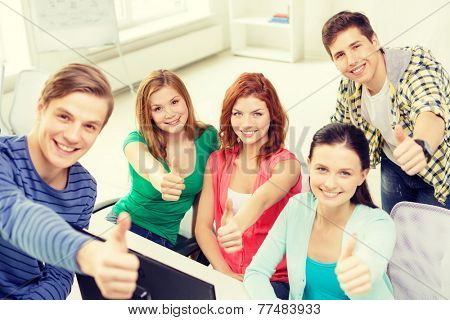 education, technology, school and people concept - group of smiling students showing thumbs up in computer class at school