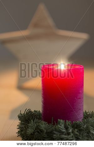 Single burning candle with star in the background