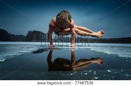 Man doing yoga exercise (parsva bakasana) on the ice of frozen lake