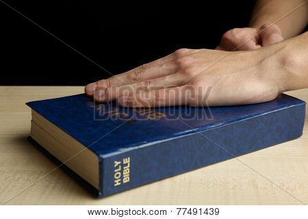 Male hands with Bible on wooden table on dark background