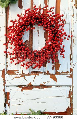 Christmas wreath of red holly berries against a vintage wooden door.