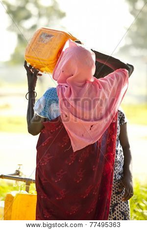 BOR, SOUTH SUDAN-JUNE 25, 2012: An unidentified South Sudanese woman drinks from a water jug at a central water filling point.