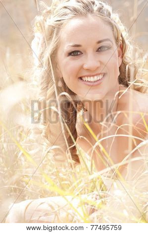Young Beautiful blonde woman walking though field with basket