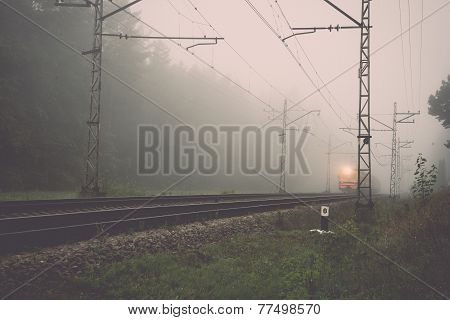Misty Country Railroad In The Early Morning With Train Incoming. Vintage.