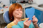 stock photo of dental  - Smiling senior woman with new dental implants sitting in the dental office and looking at the mirror - JPG