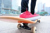 picture of skateboarding  - young woman skateboarder legs skateboarding at city - JPG