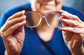 stock photo of cataracts  - Old woman hands with eyeglasses. Senior people health care. ** Note: Soft Focus at 100%, best at smaller sizes - JPG