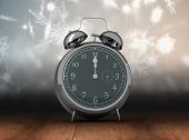 picture of count down  - Alarm clock counting down to twelve against shimmering light design over boards - JPG