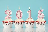picture of cupcakes  - Happy New Year for 2015 red velvet cupcakes in red and white theme with lit candles and pale blue and white background - JPG