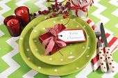 stock photo of christmas theme  - Bright colorful modern Christmas children family party table place settings in lime green red and white theme on a chevron stripe table - JPG