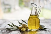 foto of olive trees  - Olive oil and olive branch on the wooden table outside - JPG