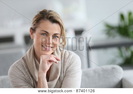 Portrait of smiling mature woman with hand on chin