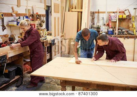 Staff Working In Busy Carpentry Workshop
