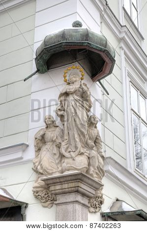 Statue of Saint or Prayer. Decoration element of house in old city. Linz, Austria