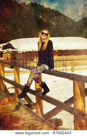 Beautiful Young Blonde Lady Posing On A Wooden Balustrade In A Snowy Winter Landscape