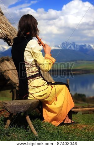 l girl in a historical costume playing her flute in an open landscape with a lake