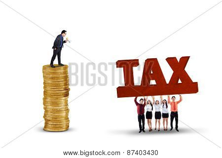 Businessman With Employees Lifting A Tax Text