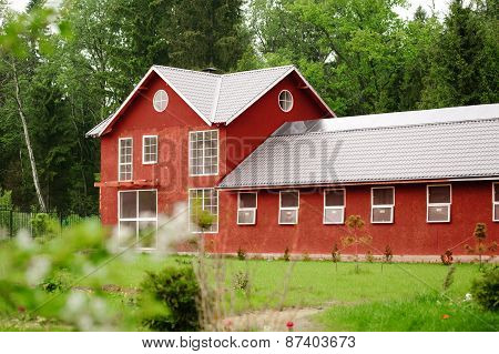 Beautiful Red Horse Barn Among The Green Forest