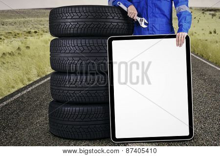 Mechanic With Tires And A Board Outdoors