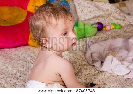 Cute blonde baby girl with beautiful blue eyes sits on bed in diapers with toy