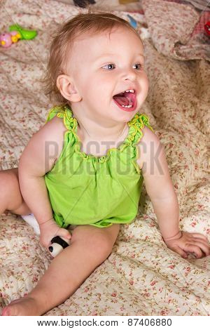 Cute blonde baby girl with beautiful blue eyes sitting and smiling with toy