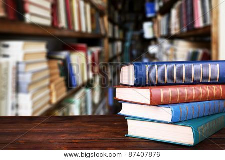 Stack of books on table on bookshelves background