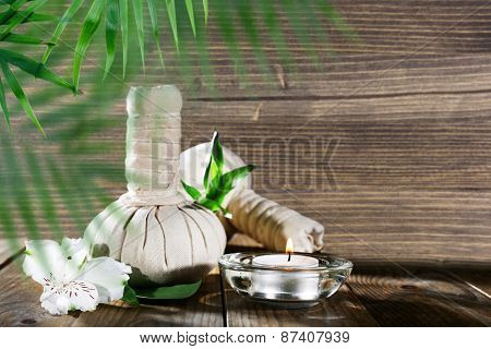 Spa compress balls with leaves on wooden background