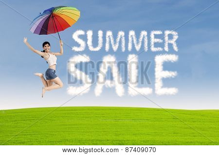 Woman Jumps With Summer Sale Sign