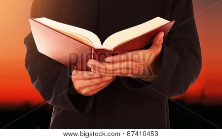 Human hands with book on sunset sky background