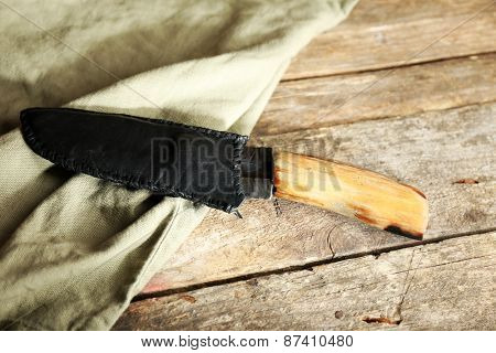 Hunting knife and sackcloth on wooden background