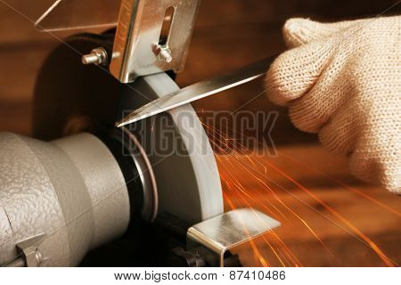 Knife sharpener and hand with blade on wooden table, closeup