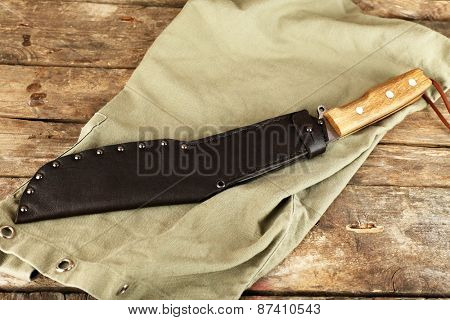 Hunting knife on wooden table with sackcloth, closeup