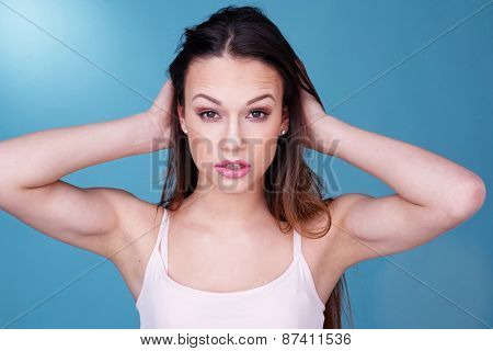 Close Up Portrait of Young Woman Wearing Tank Top with Hair in Hands Staring at Camera in front of Blue Background