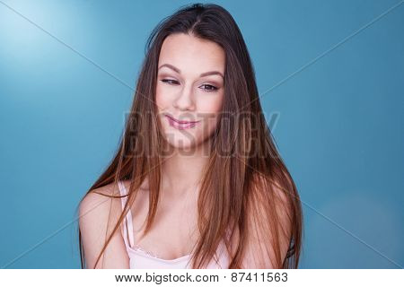 Pretty young woman with long brown hair looking down to the side with a cute whimsical smile over a blue background