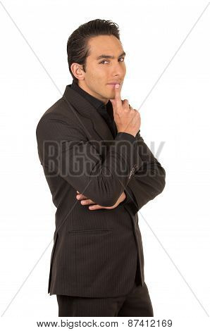 handsome young man wearing a suit posing gesturing silence